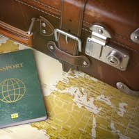 Travel or turism concept.  Old  suitcase with passport on the wo