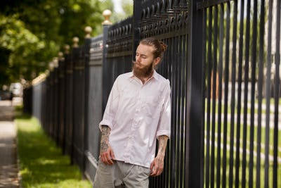 Hipster with long beard posing next to a fence