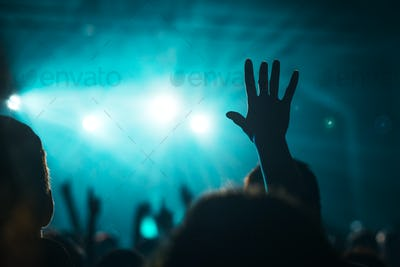Female hand raised in the air on rock music concert