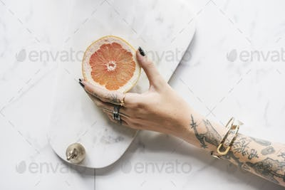 Tattoo Woman Hand Getting Orange with Marble Background