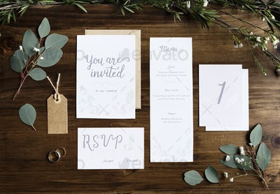 Wedding Invitation Cards Papers Laying on Table Decorate With Le