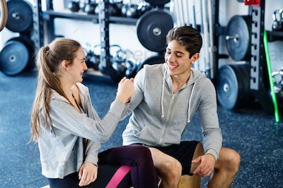 Young fit couple in crossfit gym doing fist pump.