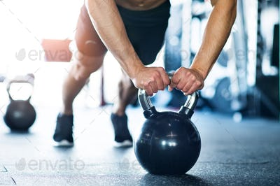 Unrecognizable fit man in gym doing push ups on kettlebells