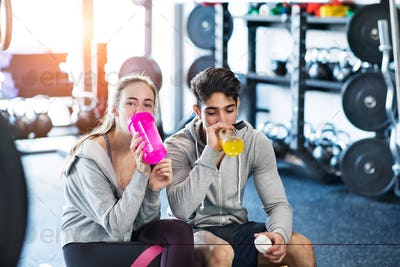 Young fit couple in modern crossfit gym drinking water.
