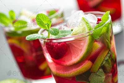 Raspberry mojito cocktail with lime, mint and ice, cold refreshing drink