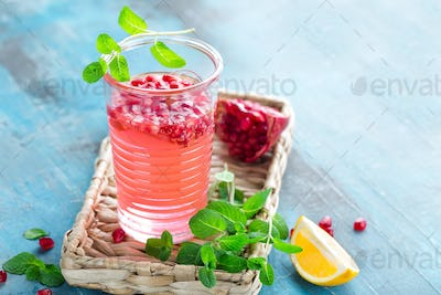 Infused pomegranate water with fresh lemon and ice, cold healthy refreshing and detox drink