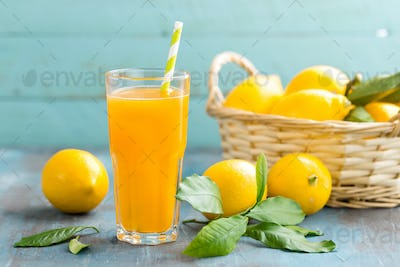 Lemon juice in glass and fresh fruits with leaves on wooden background, vitamin drink or cocktail
