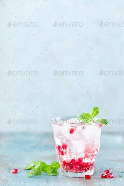 Infused water made of fresh pomegranate and mineral water with ice, cold refreshing and detox drink