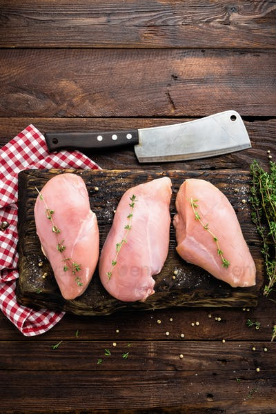 Raw chicken breasts fillets with thyme and spices on wooden cutting board on rustic background