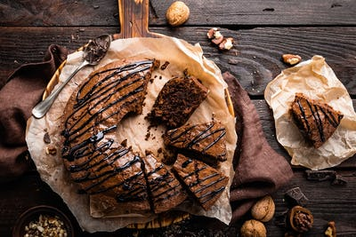 Chocolate brownie cake, dessert with nuts on dark background, top view