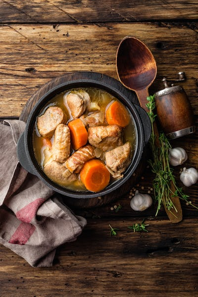 Meat stewed with carrots in sauce and spices in cast iron pot on dark wooden rustic background