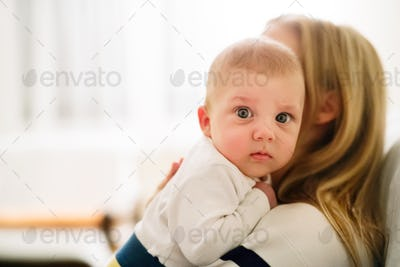 Beautiful young mother holding baby son in the arms