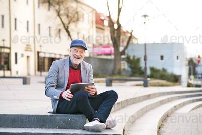 Senior man in town with tablet, making phone call