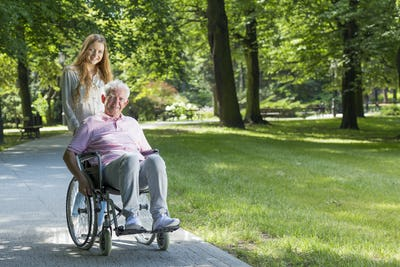 Woman with grandfather on a wheelchair in the park