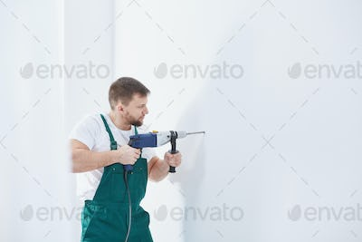 Worker drilling in a wall