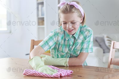 Girl wiping a table with cleaning cloth
