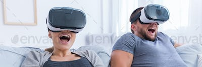 Man and woman screaming while using VR glasses