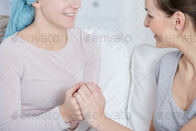 Cancer patient and her friend holding hands