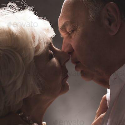Senior elegant couple kissing with love