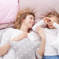 Mom and daughter laying on a bed