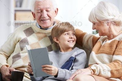 Grandparents reading book with grandson
