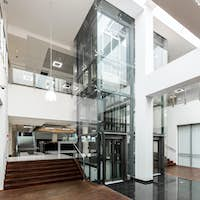 Glass lift and wooden stairs in lobby
