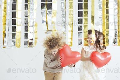 Little couple holding heart balloons