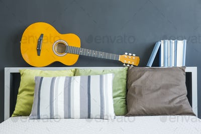 Bed with pillows, guitar and books