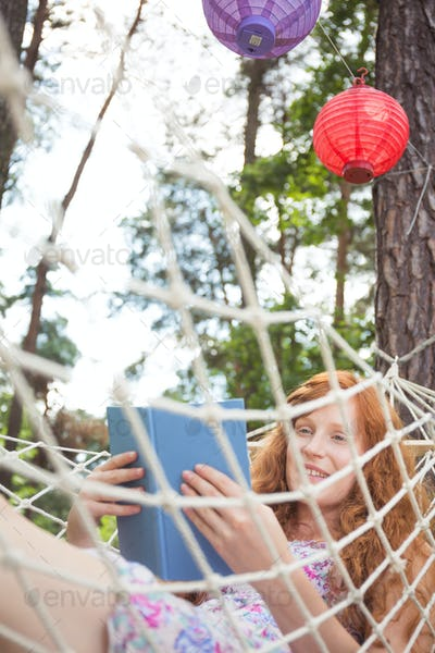 Woman reading a book on a hammock