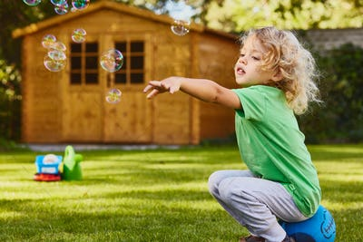 Small boy playing in garden