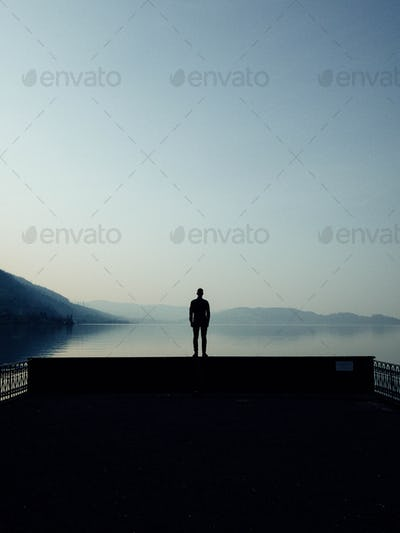 Man silhouetted against a beautiful alpine lake