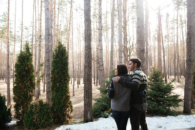 couple hugging againsr forest