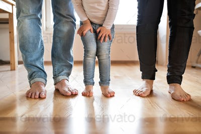 Beautiful young family. Bare feet of mother, father and daughter