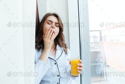 Sleepy young woman in pajamas holding orange juice and yawning