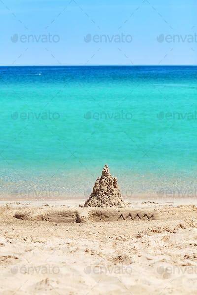 Sand castle and crocodile sculpture on beach.
