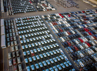 Cars trucks and buses waiting to be loaded into the cargo ship
