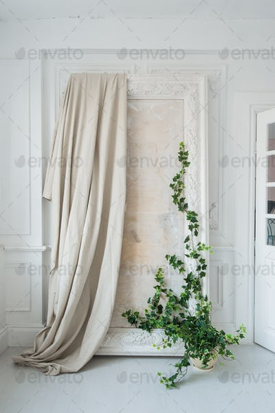 White art stucco gypsum frame for mirror with a grean loach branch on it
