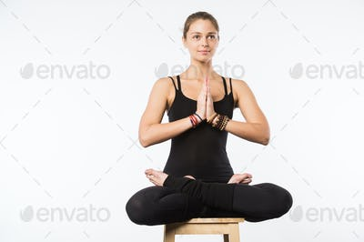 beautiful woman sit on a chair in meditative pose isolated on white