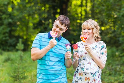 Man and pregnant woman have fun with candy