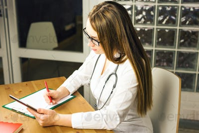 Woman medicine doctor write prescription to patient at worktable.