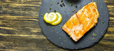 Grilled salmon steak with fresh lemon top view