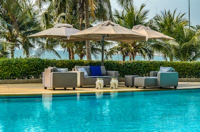 Outdoor Furniture with Umbrellas Cushions and Pillows  by the Pool
