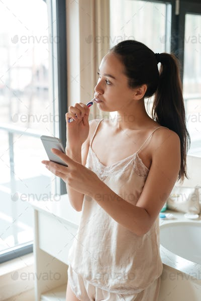 Pensive woman using mobile phone and brushing teeth in bathroom