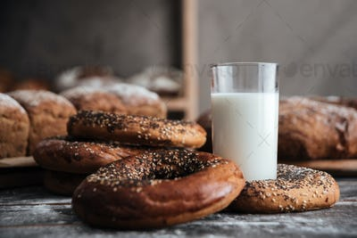 Pastries on dark table and bread on background with milk