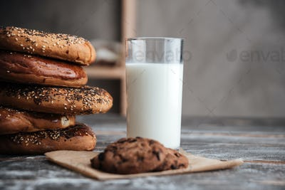Pastries on dark wooden table with milk and cookie