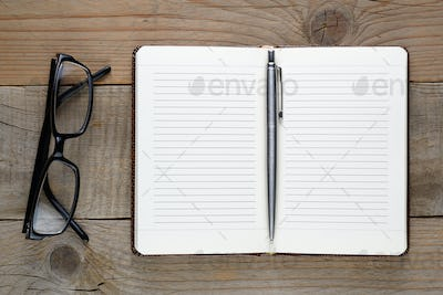 Notebook, pen and glasses on wooden table top view