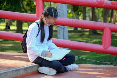 Asian schoolgirl reading a book in a park.