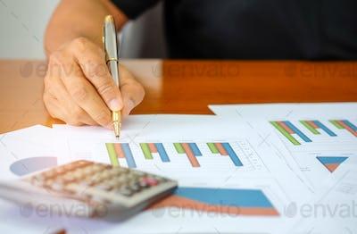 Men are using a calculator to analyze income data.
