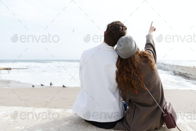Back view of couple sitting on the beach in autumn