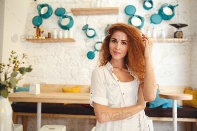 Amazing beautiful redhead young lady standing in cafe